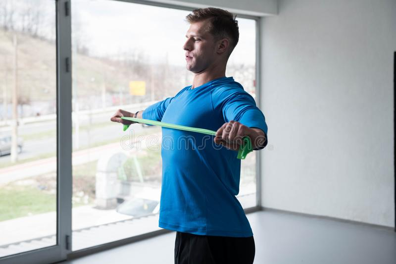 Man Warms Up With the Latex Resistance Band. Athlete in Sport Sportswear Workout With Elastic Resistance Band - Doing Shoulder Or Back Exercises in Gym stock photo