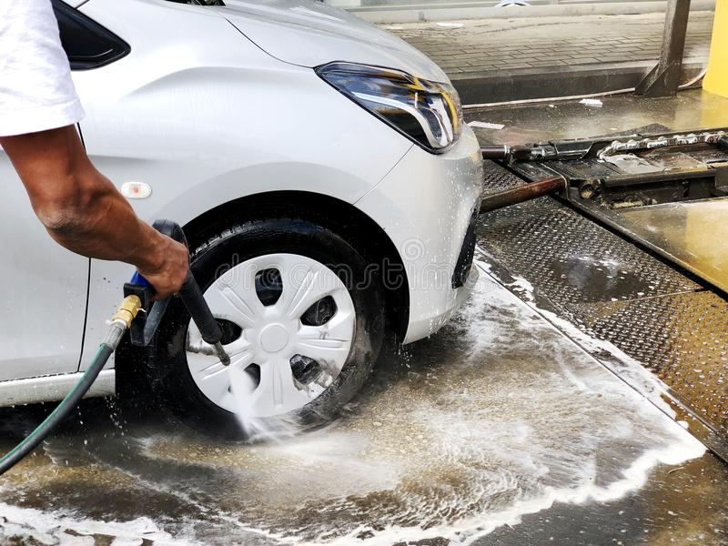 Man wash a car by hand using a foam preparation for polishing, cars in a carwash royalty free stock photography
