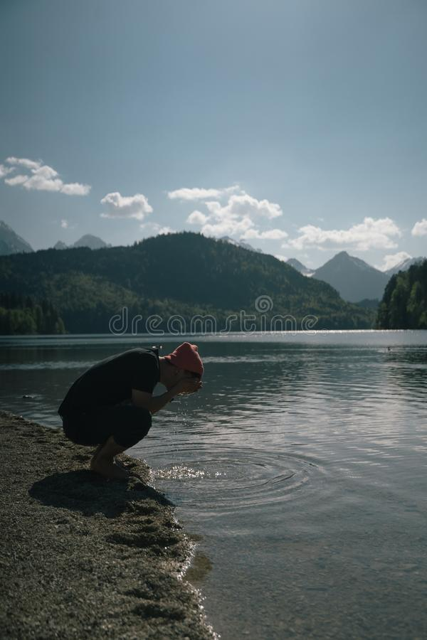 A man washes his hands on the shore of a forest lake stock photo