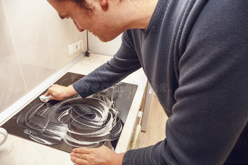 Man washes modern black electric stove with soap. Clean house royalty free stock photo