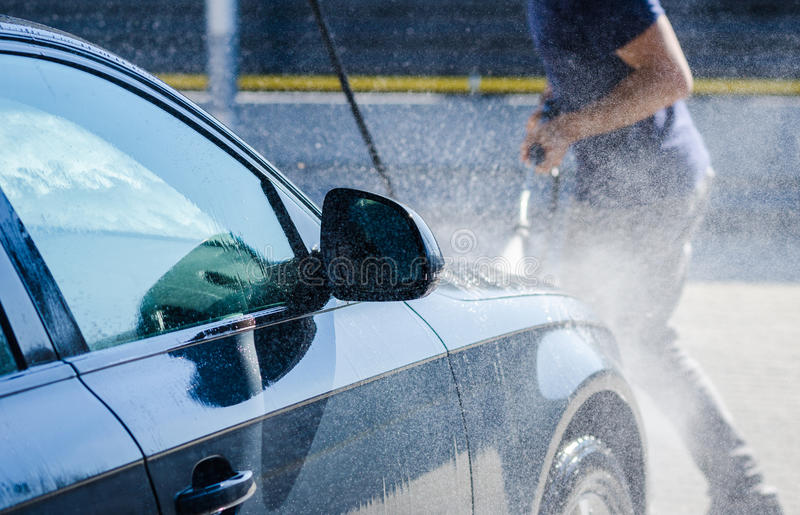 Man washing a car at the carwash. Man washing his car and pulverizing water all over with a dynamic look suggesting carwash services on a premium autovehicle royalty free stock photos