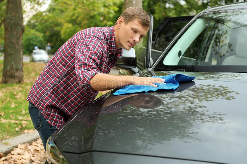 Man washing car hood with rag. Outdoors stock images