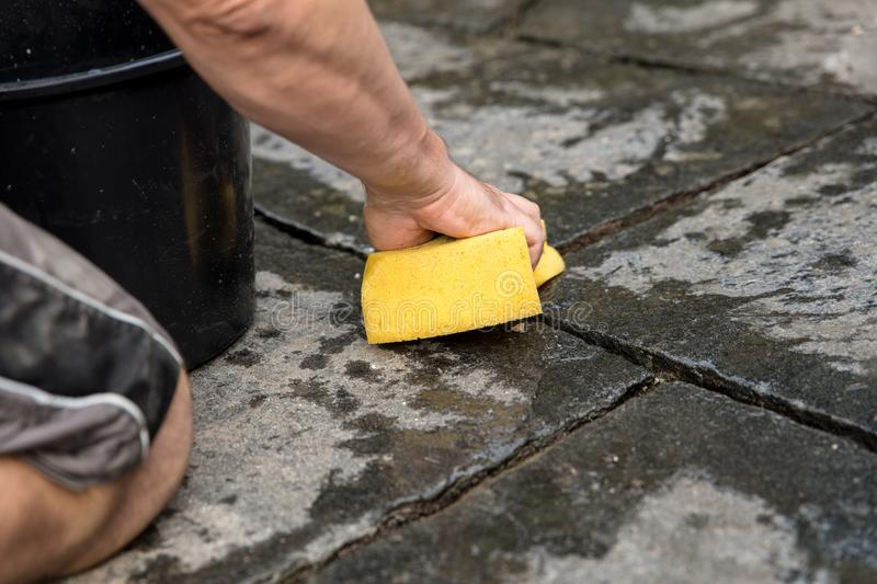 Man is washing fresh mortar joints. With a sponge stock image