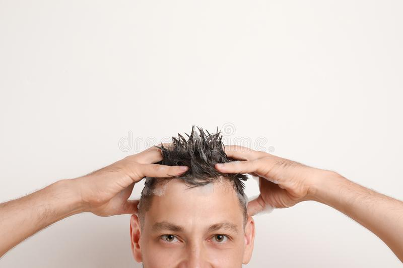 Man washing hair on white background royalty free stock photography