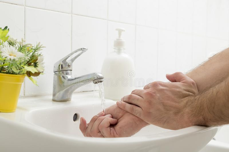 Man washing hands. Close up of a man washing hands, using liquid soap. Selective focus on hands and the tap stock photography