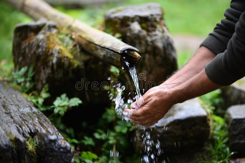 Man washing hands in fresh, cold, potable water. Of mountain spring royalty free stock photography