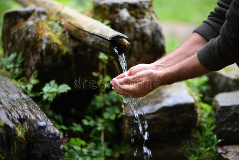 Man washing hands in fresh, cold, potable water. Of mountain spring stock image
