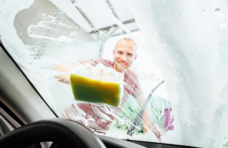 Man washing his car windshield window inside the car camera view stock photography