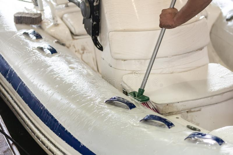 Man washing white inflatable boat with brush and pressure water system at garage. Ship service and seasonal maintenance concept.  royalty free stock images