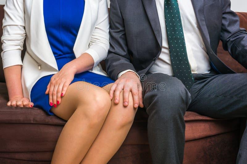 Man wat betreft vrouwen` s knie - seksuele intimidatie in bureau stock afbeelding