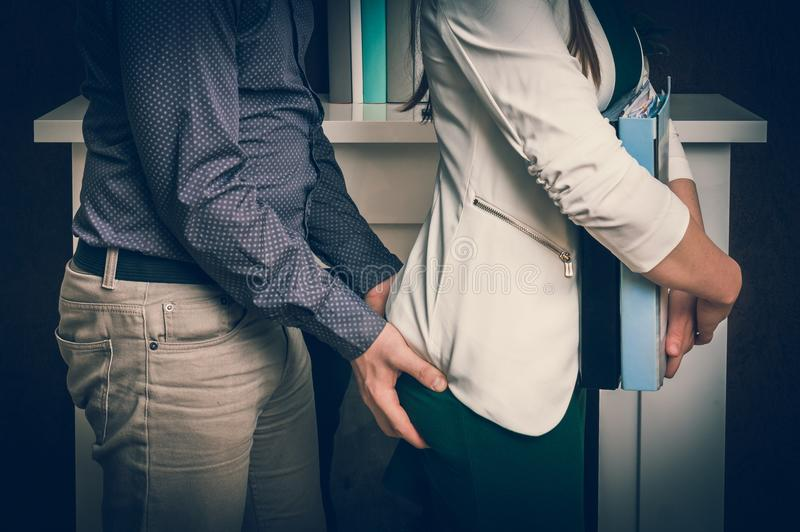 Man wat betreft vrouwen` s uiteinde - seksuele intimidatie in bureau stock afbeelding