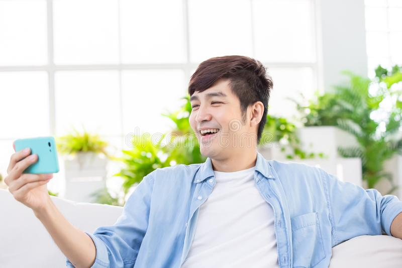 Man watch video with phone. Man watch video with smart phone and laughing royalty free stock photos