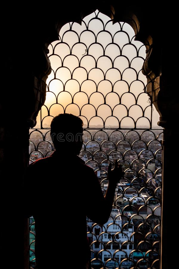 Man watches a sunset from Jama Masjid mosque in the center of Delhi, Indi. A royalty free stock photos