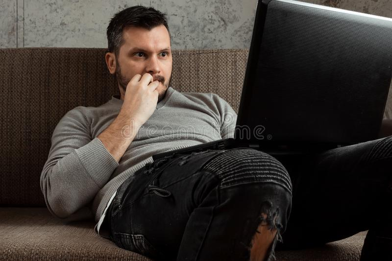 A man watches a video in a laptop while sitting on the couch is very surprised. Concept porn videos, admiration, desire. Smile, human emotions stock photo