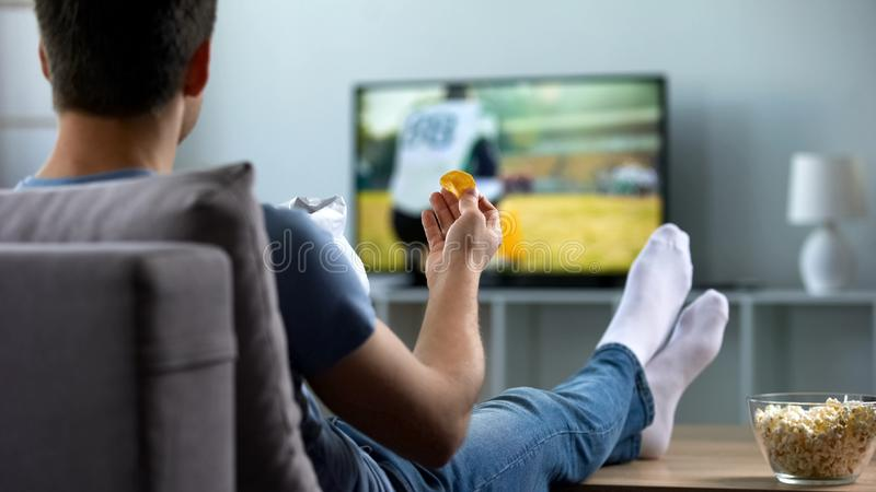 Man watching american football eating snacks on couch home, weekend leisure. Stock photo royalty free stock photography