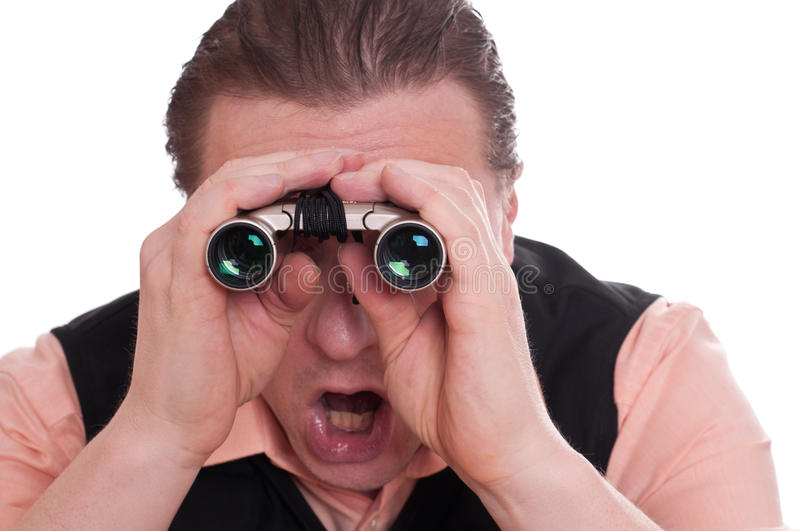 Man is watching astonished with a binoculars stock photo