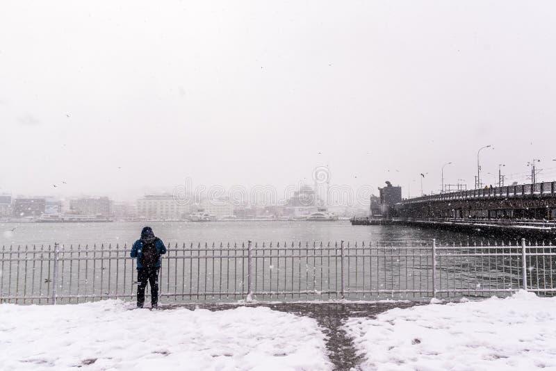 Man watching bosphorus on the heaviest snowfall. Unidentified man watching bosphorus on the heaviest snowfall in Istanbul,Turkey royalty free stock photo