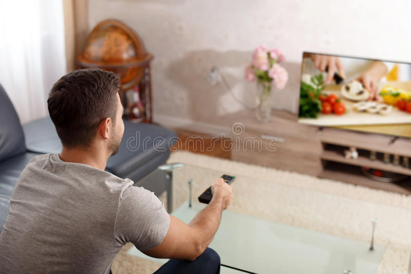 Man watching cooking tutorial in TV. Excited man watching cooking tutorial in TV, pushing button on remote control royalty free stock photos