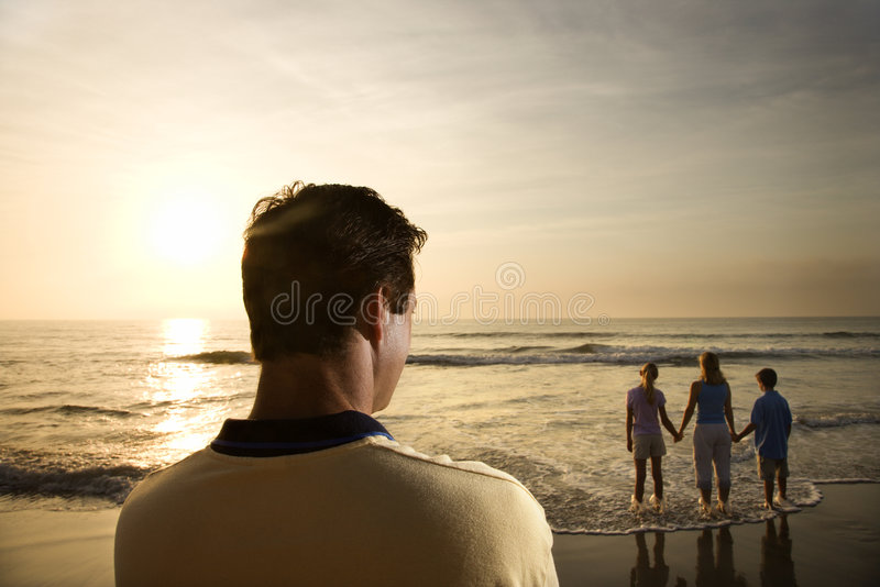 Man watching family at beach royalty free stock photography