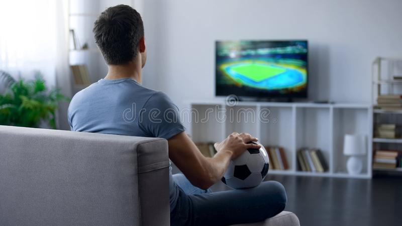 Man watching game on tv at home supporting one of soccer team, match result stock photo