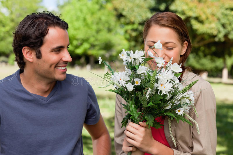 Download Man Watching His Friend Smell A Bunch Of Flowers Royalty Free Stock Photos - Image: 25332108