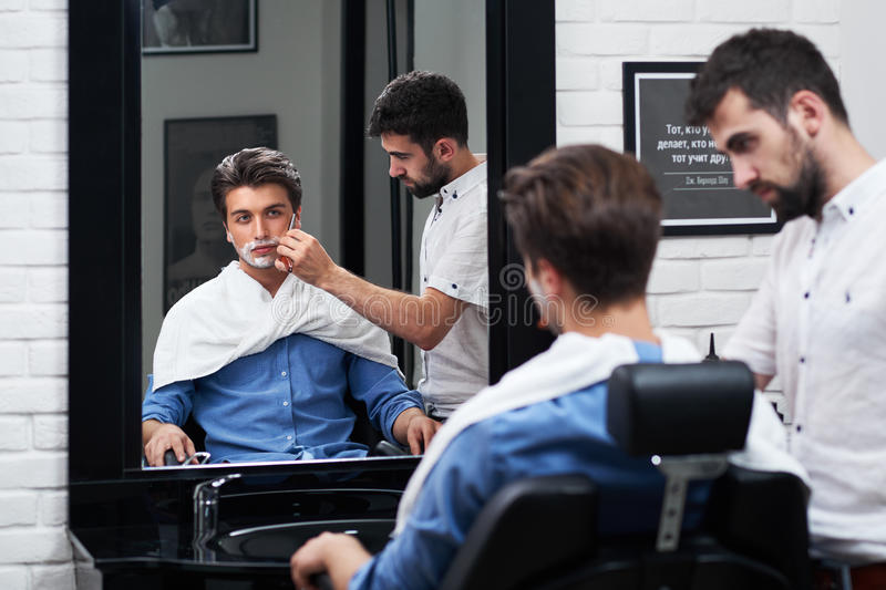 Man watching in the mirror for shaving process in Barbershop. royalty free stock images
