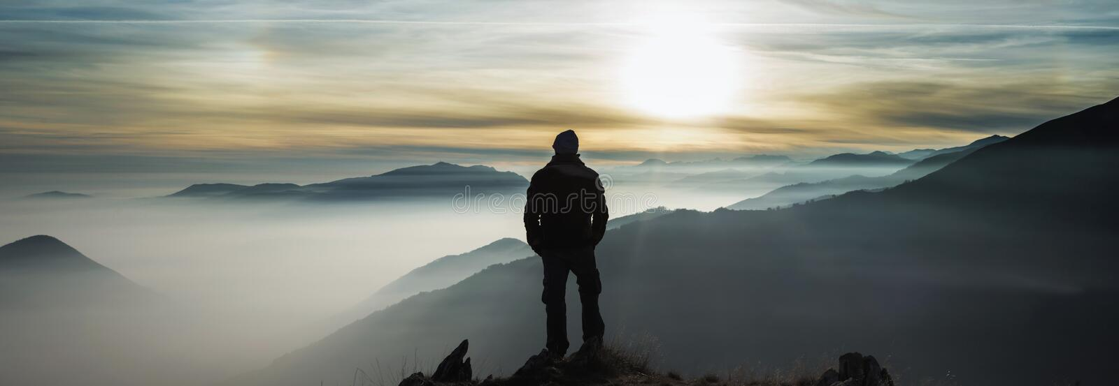 Man watching mountains clouds from a peak stock photos