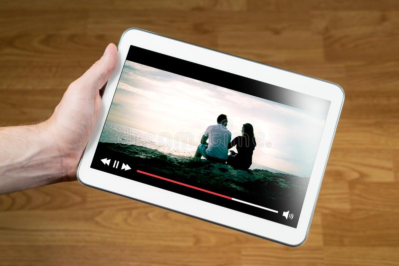 Man watching movie online with mobile device. Hand holding tablet with imaginary video player and film streaming service stock photography