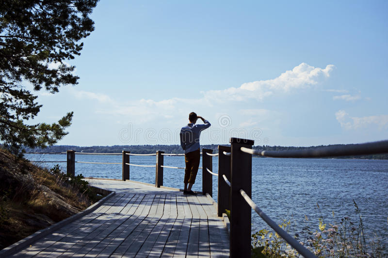 Man looking out over archipelago in summer. Man looking out over the beautiful archipelago of Stockholm a sunny summer day royalty free stock photo