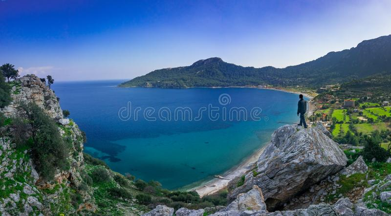 The man watching the panoramic view of marmaris, on the edge of the cliff. Kumlubuk, Marmaris, Turkey. Holiday and travel. The man watching the panoramic view of royalty free stock images
