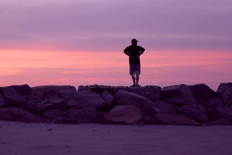 Man Watching a Pink and Violet Sunset at the Beach. A man standing on the rocks of a breakwater at a beach watching the pink and violet clouds as the sun is