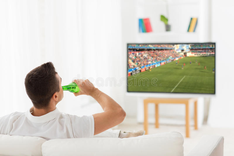 Man watching soccer game on tv and drinking beer. Leisure, technology, mass media and people concept - man watching football or soccer game on tv and drinking stock photography