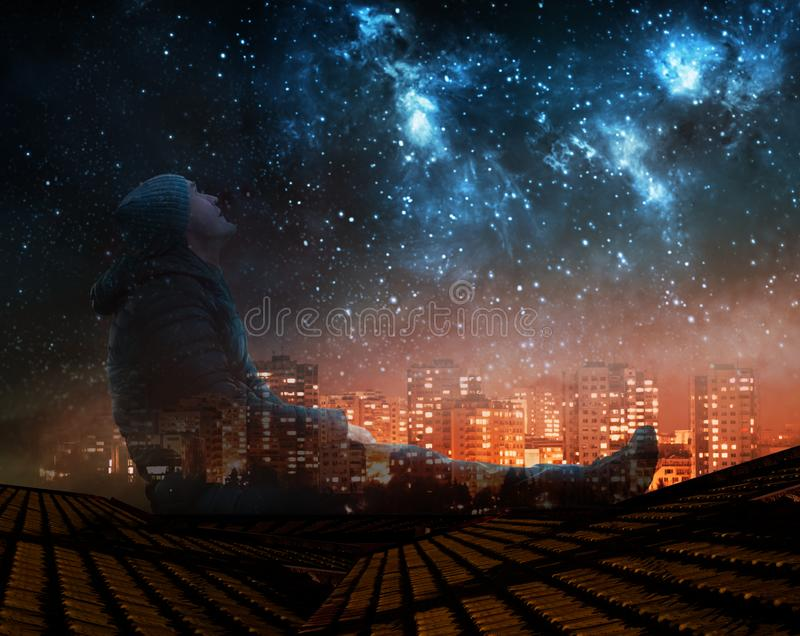 A man watching the stars in night sky on roof in city stock illustration