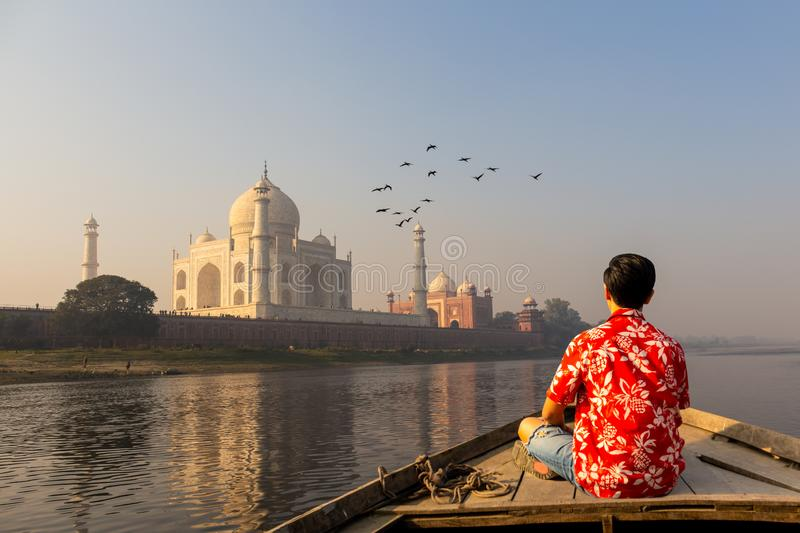 Man watching sunset over Taj Mahal from a wooden boat with bird flying over. stock image
