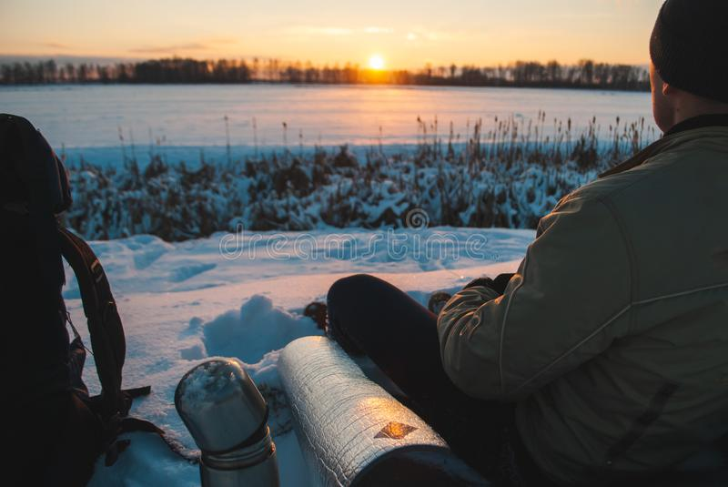 Man watching the sunset in the winter evening, winter tourism, camping in the snow close-up, stock photography