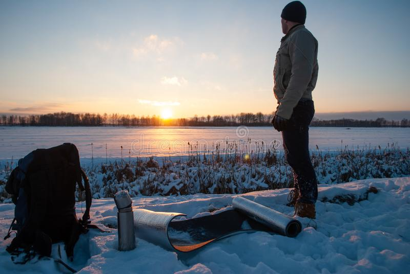 Man watching the sunset in the winter evening, winter tourism, camping in the snow, stock photos