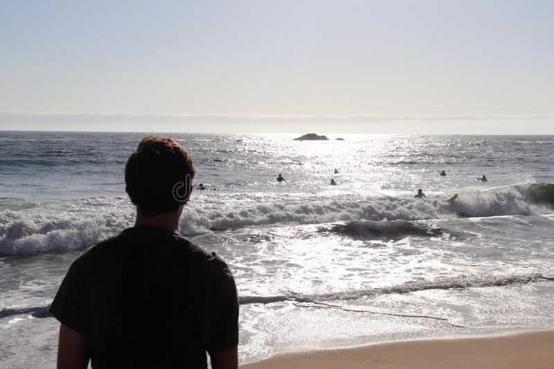 Man watching surfers royalty free stock photography