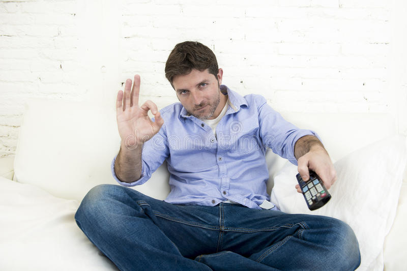 Man watching television at living room sofa with remote control smiling giving okay hand sign stock image