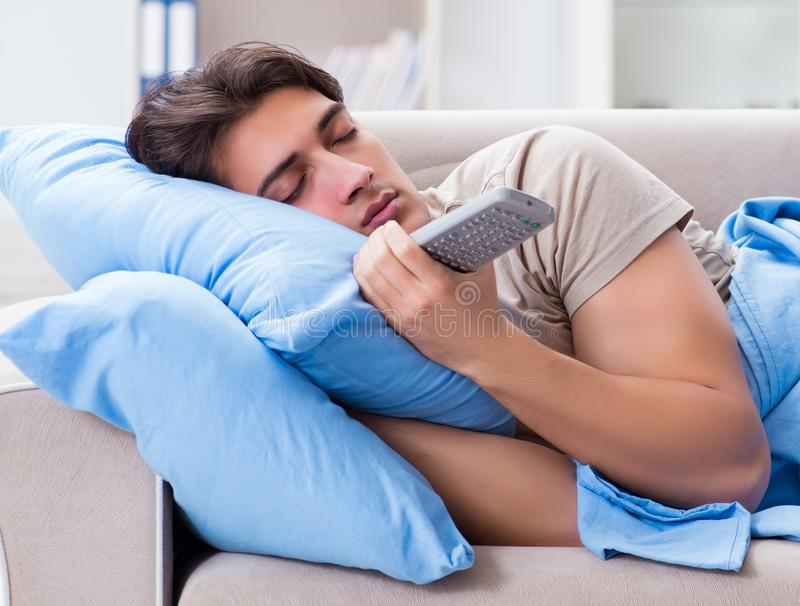 Man watching tv from bed holding remote control unit. The man watching tv from bed holding remote control unit stock image
