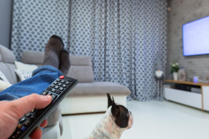 Man watching TV in living room with remote control stock photo