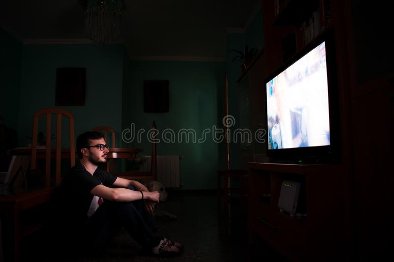 Man watching tv and zapping sitting on the floor at home stock photography