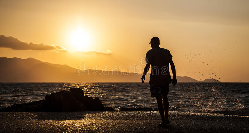 Man and waves splashing on a beautiful sunset royalty free stock photography