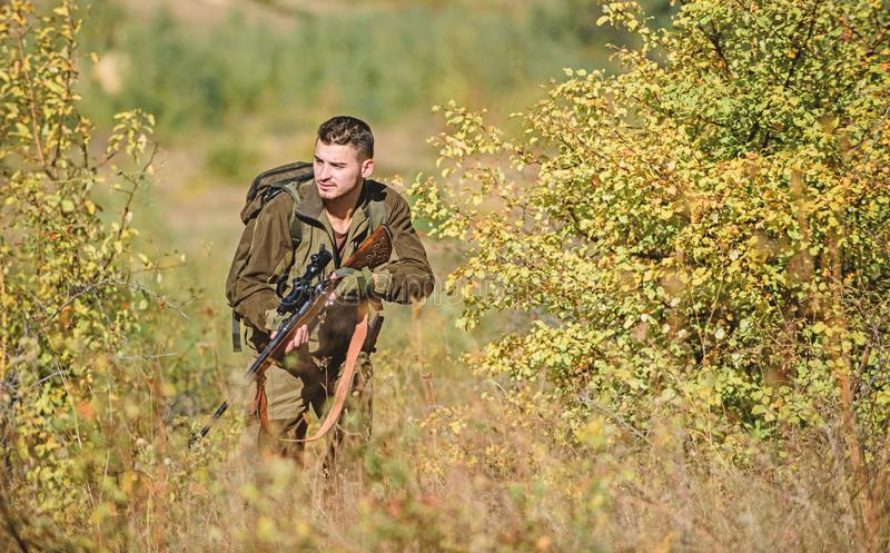 Man wear camouflage clothes nature background. Hunting permit. Hunting is brutal masculine hobby. Hunting equipment for stock images