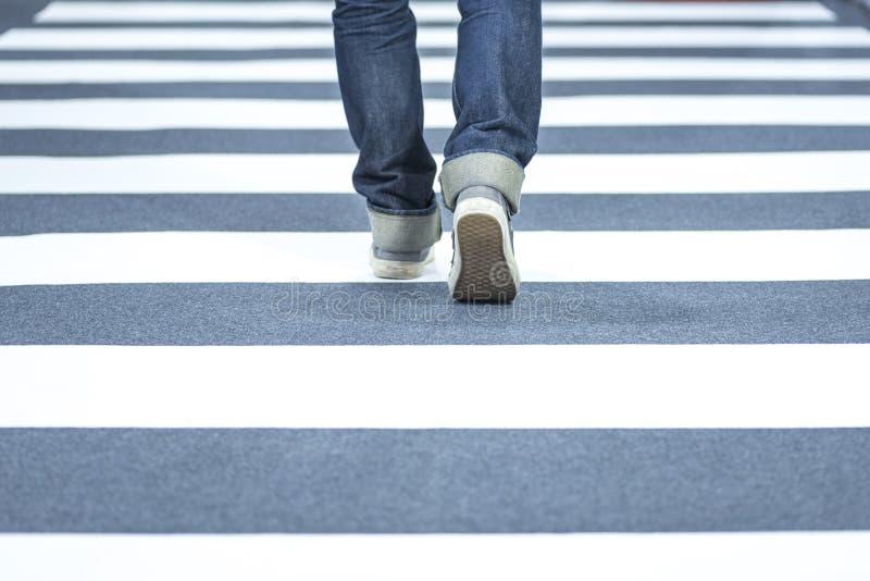 Man wear jeans walk across the street on the crosswalk royalty free stock photography