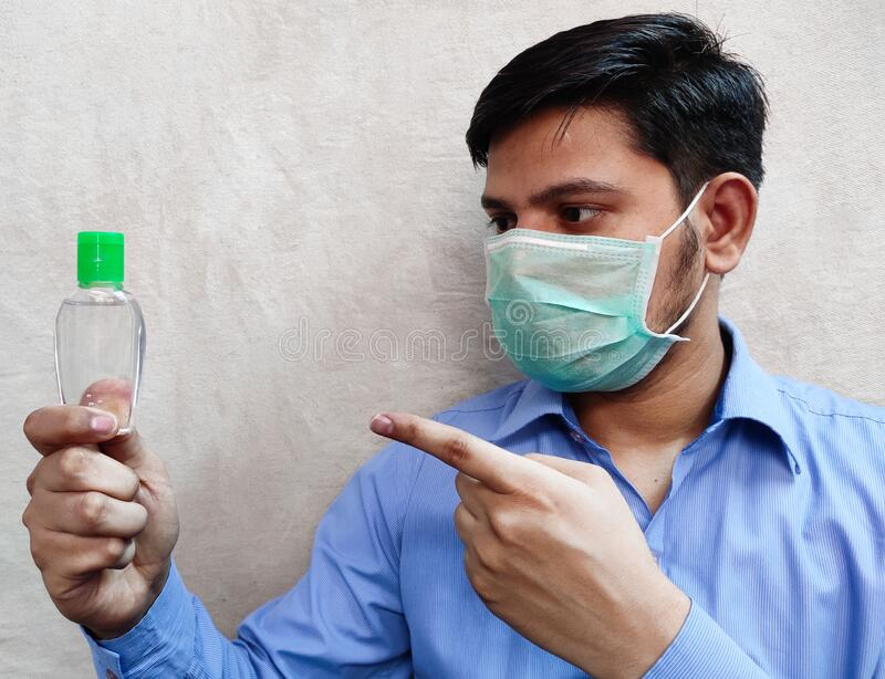 Man wear mask holding sanitizer in left pointing by hand right hand index finger. Man wear mask holding sanitizer in right hand,  pointing by hand left hand stock photo