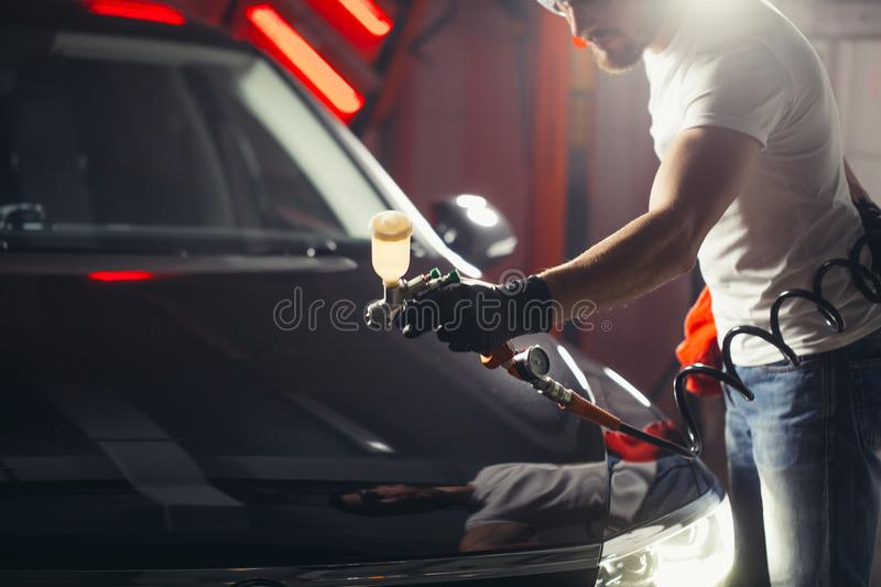 Car wash and coating business with ceramic coating.Spraying varnish to car. royalty free stock photo