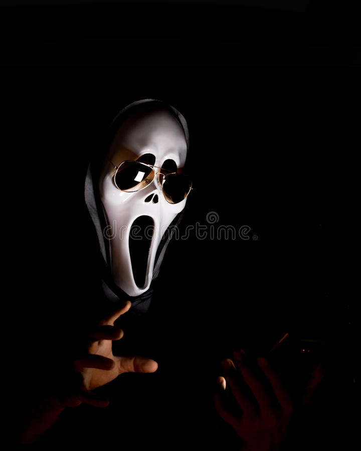 Man wear spooky halloween mask and sunglasses looking tablet in. Hand on a black background royalty free stock photos