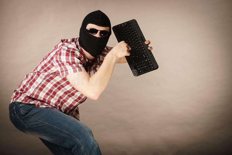 Man wearing balaclava holding keyboard royalty free stock photo