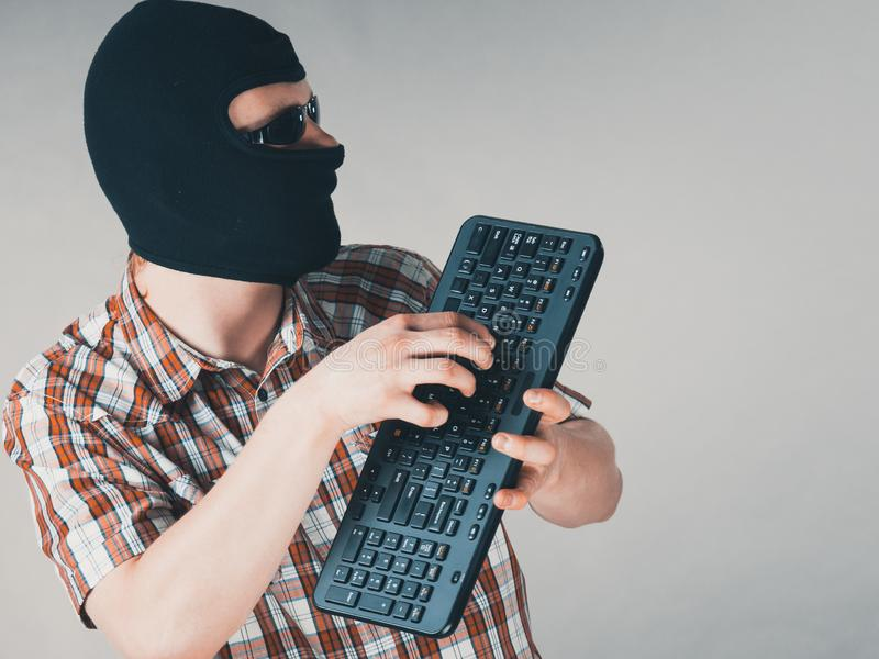 Man wearing balaclava holding keyboard stock photos