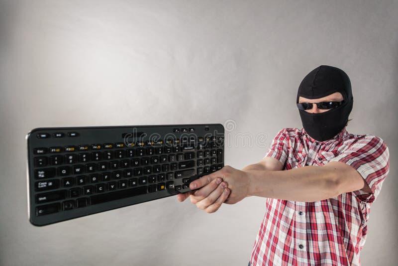 Man wearing balaclava shooting from keyboard royalty free stock photos